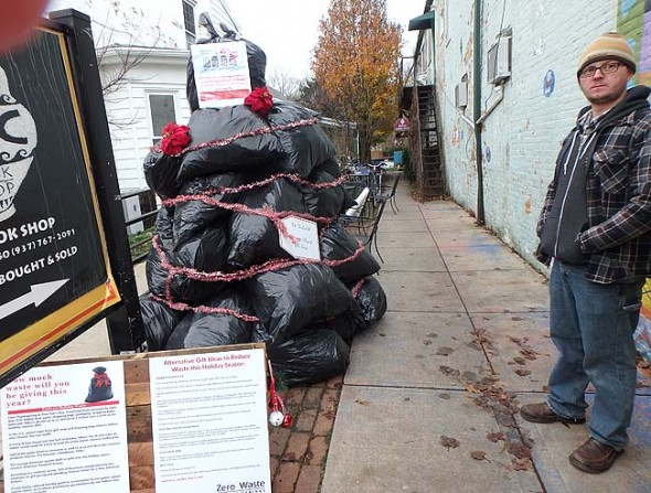 """Tom Clevenger, a member of Zero Waste Yellow Springs, a group affiliated with the YS Resilience Network, stands next to the """"Trash Tree"""" they created to raise awareness around issues of consumption and waste during the holidays. The tree, made of trash bags stuffed with newspaper, proved surprisingly controversial. Erected in the alley next to the Emporium, it was up for just four days last week; it was damaged and, ultimately, dismantled before group members took the remainder of the tree down last Thursday. (submitted photo)"""