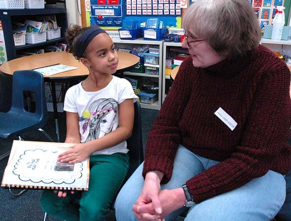 Mills Lawn second-grader Lillianna Sylvester showed her original story to Nancy Hirsch during last week's Memories Party at the school. The party was the culmination of a project-based learning project aimed at developing empathy in youngsters by sharing memories with Yellow Springs seniors. (Photo by Matt Minde)
