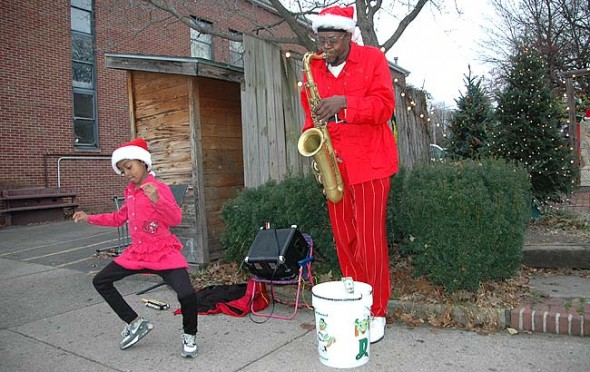 Dayton musician Tumust Allison and his daughter, Angel, added to the holiday spirit last weekend in downtown Yellow Springs. (Photo by Diane Chiddister)