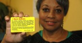 Mijanou Marretta-Lewis, a Yellow Springs resident and mother of two autistic boys, holds a card designed to facilitate easier interactions between people with autism and police. The cards explain why the bearer may have trouble understanding the situation, as police may not be aware of the sensitivities of people with autism. The cards are available at the Yellow Springs Police Department. (photo by Suzanne Szempruch)