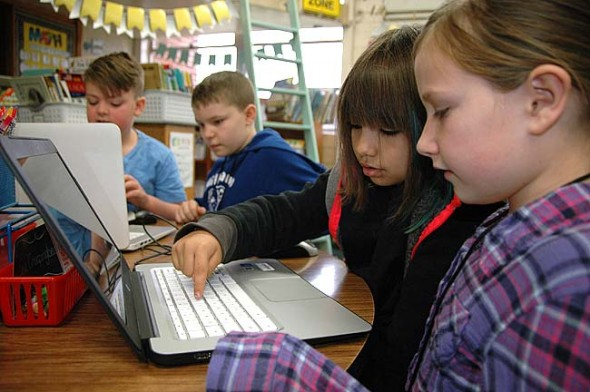 """From left, Jack Hutchings, Maddox Fry, Era Creepingbear and Alayna Hamilton were among the Mills Lawn students who took part in Hour of Code last week, an international movement designed to introduce children of all ages to computer science and coding. Megan Bennett's third-grade class was already ahead of the curve, having completed a project-based learning, or PBL, project called """"Coding Cadets"""" this fall. The third graders took their coding knowledge to their older and younger peers, coaching each Mills Lawn class in the basics of creating with code. (Photo by Audrey Hackett)"""