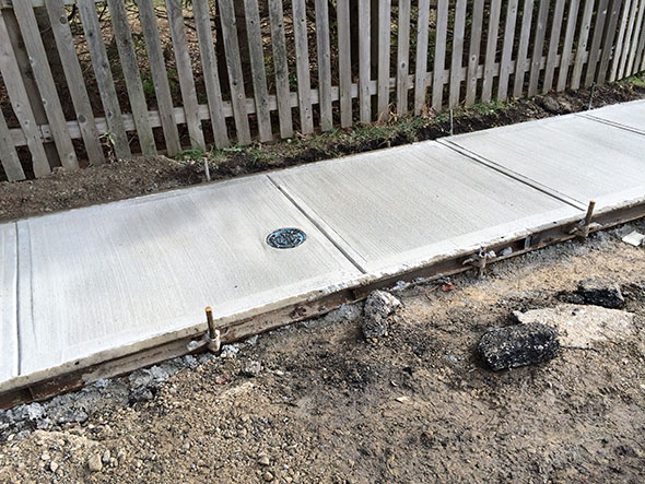 concrete sidewalk curing in its form