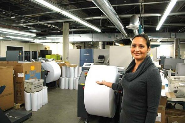 DMS President Christine Soward showed off one of the company's newest acquisitions, a massive inkjet printer capable of handling 25,000 sheets of paper per hour. Currently located in downtown Dayton, the 32-year-old company is poised to purchase 888 Dayton St. in Yellow Springs, former home of the Antioch Company and Creative Memories, and move its headquarters and most of its production there. (Photo by Audrey Hackett)