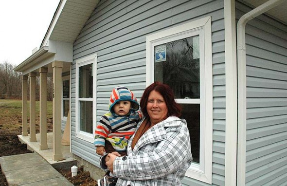 "New first-time homebuyer Julie McCowan, holding her grandson, Dylann, in front of the Cemetery Street home she recently purchased through Home, Inc. for her four-person family (plus frequent visits from ""little ones"" like Dylann, she said). Villagers wishing to celebrate with McCowan and her family and learn more about Home, Inc.'s Cemetery Street development are invited to an open house at 138 Cemetery St. on Friday, Jan. 29, from 5 to 7 p.m. (Photo by Audrey Hackett)"