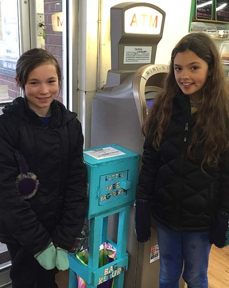 Lily Rainey, 12, left, and Carina Basora, 11, stand next to the baggerie they installed at Tom's Market, which allows patrons to borrow and return canvas bags. The baggerie was built as part of their team's participation in the First Lego League competition, and reflects the competition's theme of dealing with trash. The team was inspired to reduce the use of plastic grocery bags, which they found through research to be immensely harmful to the earth, its animals and its people. (submitted Photo)