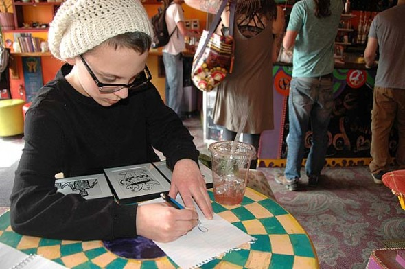 "Young artist Christian Salvatore demonstrated his sketching skills at the Spirited Goat last week. On March 5 through the end of the month, the coffeehouse will host a show of his ""zentangle"" artwork. Pieces will be for sale (pay what you believe they're worth) and proceeds will support Christian's attendance at a computer coding summer camp at OSU. (Photo by Audrey Hackett)"