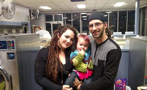 Artist Anna Burke and musician Ryan Stinson, with their daughter, Presley, 18 months, on a recent evening at the laundromat on Dayton Street. Burke and Stinson each moved to Yellow Springs in 2012 from nearby communities. They met here and have begun to build a life in the village, loving the community and navigating the challenges of housing, employment, parenthood and pursuing their art. (Photo by Dylan Taylor-Lehman)