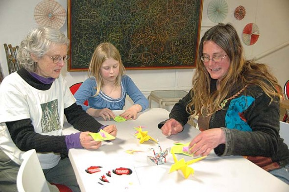 About a dozen villagers learned to make origami cranes, frogs and more last Saturday night at the Yellow Springs Arts Council, among them, from left, Fern Opotow, Areya Harker and Lara Bauer. (Photo by Audrey Hackett)