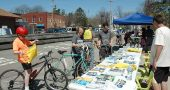 """Opening Day for Trails"" drew crowds of cyclists and walkers last Saturday, the bluest of a blue string of spring days. Brian Housh, right, Midwest policy manager for Rails-to-Trails, staffed the information table in front of the Yellow Springs train station, where cyclists stopped for trail brochures, maps, faux ""tattoos,"" t-shirts and more. (Photo by Audrey Hackett)"
