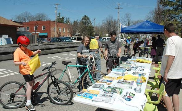 """Opening Day for Trails"" drew crowds of cyclists and walkers last Saturday, the bluest of a blue string of spring days. Cyclists stopped in front of the Yellow Springs train station for trail brochures, maps, faux ""tattoos,"" t-shirts and more. (Photo by Audrey Hackett)"