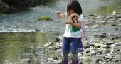 In Antioch School's Forest Kindergarten program, the outdoors serves as laboratory and playground. Pictured, Kaede Eto took water samples from the river last month — while also holding fast to her doll. (Photo by Carol Simmons)