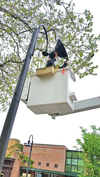 Village electric workers installed new streetlamps downtown on Wednesday morning. (photo by Kathryn Hitchcock)