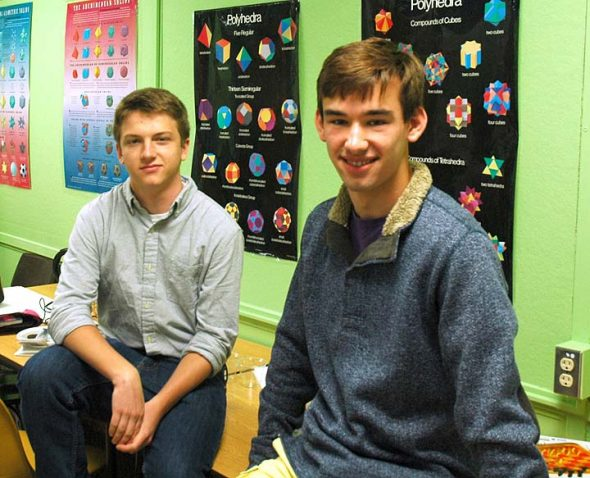 """2016 YSHS salutatorian Henry Potts-Rubin, left, and valedictorian Gabriel Day sat in front of posters of their favorite subject, math. The two have a broad range of interests, spanning scholarship, sports and art, and both express an immense love of learning for the sake of learning. School counselor Dave Smith said the two are representative of a remarkable senior class, and one that is made up of """"hardworking and lovely people."""" (Photo by Dylan Taylor-Lehman)"""