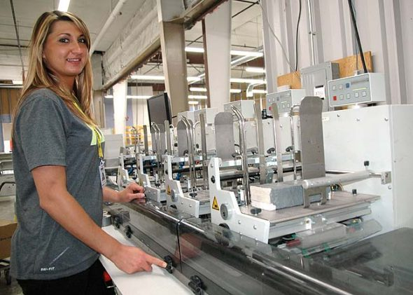 "DMS ink, which purchased the former Antioch Publishing facility in early winter, was recently honored for its fast growth rate. Pictured above is the company's assistant manager of production, Tiffany Simpson, with the ""intelligent inserter,"" which folds, inserts, counts and prints materials all in one process. The company can print 60 million pieces of direct mail a month. (Photo by Diane Chiddister)"