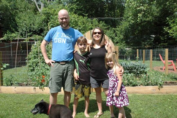 "The Oberg family, from left, Eric, Cole, Kelley and Sage (plus 17-year-old dog, Larsen), moved to Yellow Springs in 2014 seeking an open and tolerant community. Intrepid adventurers, Eric, born and raised in Alaska, and Kelley, who lived there for many years, are ""homesteading"" on a small scale at their Fair Acres residence, including by planting the gardens pictured here. (Photo by Audrey Hackett)"