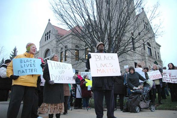 Yellow Springs residents played a large role in calling for justice after the 2014 police shooting of John Crawford III in a Beavercreek Walmart. Here, from left, villagers Joan Chappelle, Cheryl Smith and Bomani Moyenda were among area residents demonstrating at the Greene County courthouse in Xenia in December of 2014. Nearly two years after Crawford's shooting, many questions remain. (News archive Photo by Lauren Heaton)