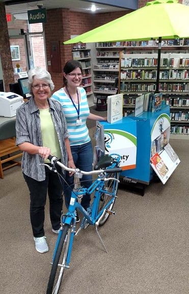 Yellow Springs head librarian Connie Collett (left) and librarian Krista Lackey stand next to the Greene County Library System's mobile bike library, which made its debut in the Yellow Springs 4th of July parade. The bike will appear at different events and places in Yellow Springs and Greene County over the summer, delivering books and helping people learn about the library. (Photo by Dylan Taylor-Lehman)