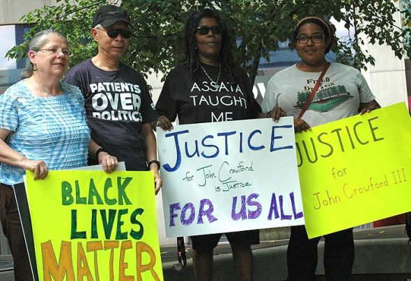 People gathered last Saturday, July 30, at Courthouse Square in Dayton to protest the delay in the Department of Justice investigation of the police shooting death of John Crawford III, which took place Aug. 5, 2014. Shown above are, from left, Lynn Buffington and Don Nguyen of Beavercreek and Ndidi Achebe and Rachel Feltner of Dayton. (Photo by Diane Chiddister)