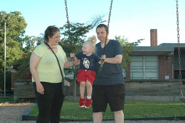 Villagers Tanya Maus and James Luckett romped with their son, August Frederick Townes, at the Mills Lawn playground on a recent evening. Maus and Luckett moved to Yellow Springs in 2013, and August was born six months later. This summer, the family put down permanent roots, buying a home through Home, Inc. (Photo by Audrey Hackett)