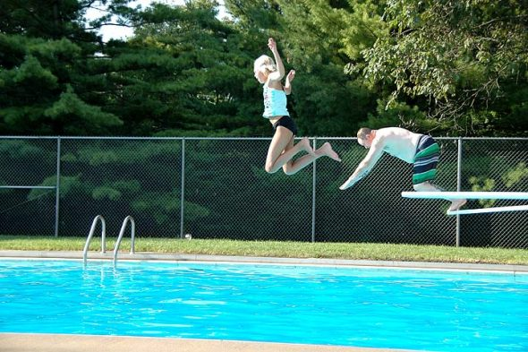 The prosepect of hitting the water after a flying leap was made more attractive by the promise of a cool splash, as local Siobhan and her uncle Christian, visiting from Jamestown, saltoed through the summer air at Gaunt Park Pool last Friday. (Photo by Isaac Delamatre)