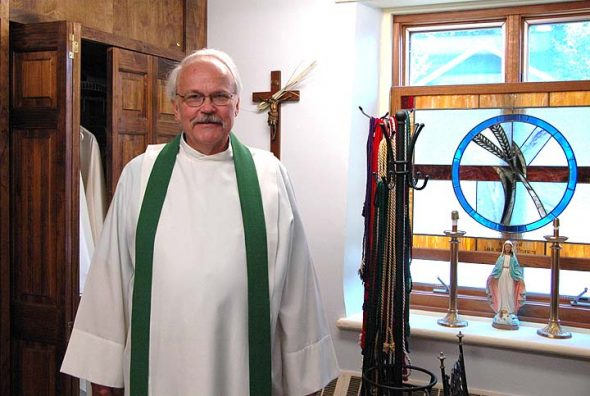 St. Paul Church's new pastor, Father John Krumm, stood in the local church's vestry after mass on a recent morning. Krumm, who also leads churches in Xenia and Jamestown, began a six-year appointment at St. Paul on July 1, replacing former pastor Father Anthony Geraci. Some parishioners hope Krumm will help heal divides the local church community has suffered in recent years. (Photo by Audrey Haclett)