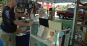 The 36th Annual Yellow Springs Book Fair takes place on Saturday, Aug. 20, from 8 a.m. to 4 p.m. at Mills Lawn School grounds. Shown above, Blue Jacket Books owner Laurence Hammar is shown at last year's fair with villager Anne Johnson.