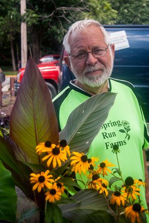 Paul Snyder of Spring Run Farms poses behind the leaves of a Canna plant.