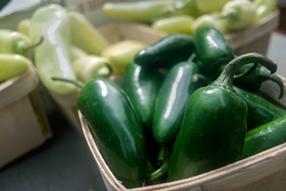 Jalapenos glisten in the market sun.