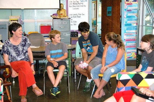 Everyone has a turn to talk and share during the daily morning meeting of the Antioch School's Older Group. The OG has a new teacher, Sally Dennis (far left), and teaching assistant, Matt Moon (third from left) this year. Student Luka Sage-Frabotta sits between them during Tuesday's meeting time; classmates Mia Florkey and Luca Acheson sit to the right. (Photo by Carol Simmons)