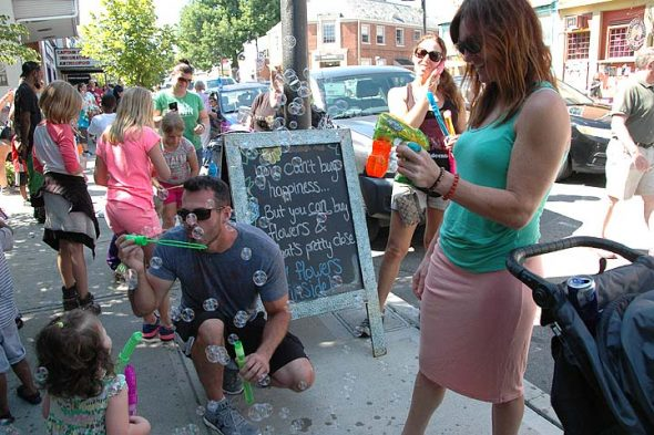 Justin and Jennifer Stafford of Oakwood, kneeling and at right, and their daughter, Harper, left bottom corner, were among the bubble-lovers who visited Yellow Springs on Sunday to take part in the annual Bubblefest. (Photo by Diane Chiddister)