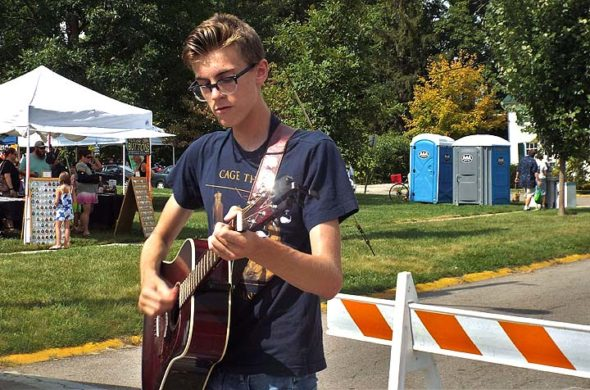 Young musician Noah Krier was spotted busking at Cyclops Fest this past Saturday. (Photo by Holly Gillenwater)