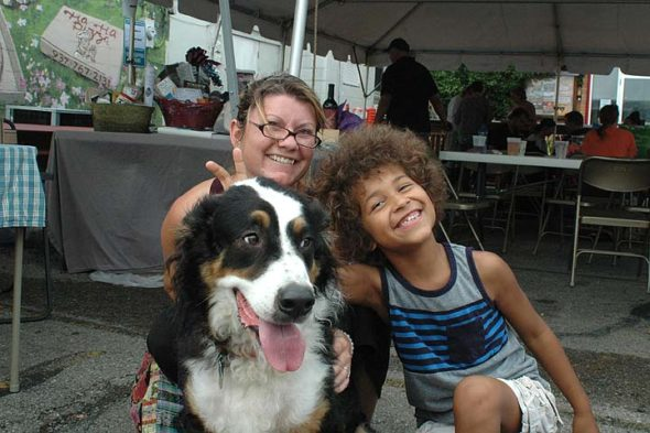 Villagers Charlotte Toms and her son, Jaden, posed with the family's dog, Biscuit, at Dog Day this past Saturday. (Photo by Audrey Hackett)