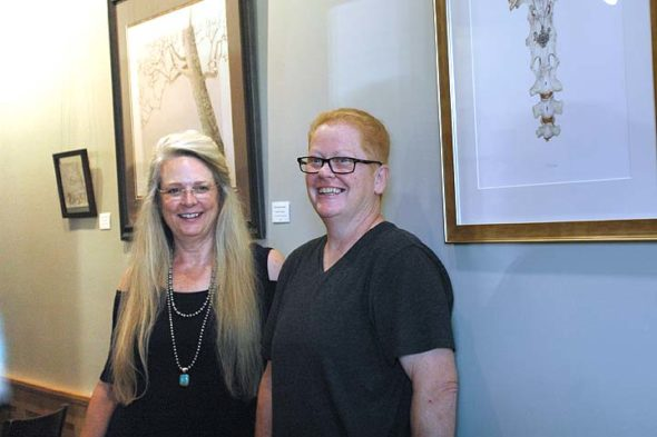 "'Migrations,' a new art exhibition on display through October at The Winds Cafe and Bakery, features watercolors by Cathy Ledeker, left, and pen-and-ink and Prismacolor works by Penelope 'Penny' S. Adamson. The show is rooted in a 10-year friendship between the women tied to family and place. Around the corner from the Winds, the YS Arts Council Gallery is hosting a separate two-person exhibition, ""Shared Views,"" through Oct. 16. The Arts Council show features 25 pairs of paintings by villagers Sherraid Scott and Sigalia Cannon, who for more than 20 years have meet most Sundays to paint side-by-side at sites at various area locales. (Photo by Carol Simmons)"