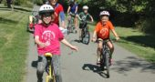 """More than 30 riders took off under blue skies and a hot sun last Sunday for the Antioch School's annual """"Anything on Wheels"""" fundraiser. Riders — including Antioch school student Lucy Dennis (on unicyle), Older Group teacher Sally Dennis and students Elijah Moon and Ayla Current — pedaled down the Little Miami Scenic Trail for all or part of a 15-mile round-trip route to the northern edge of Xenia. (Photo by Audrey Hackett)"""