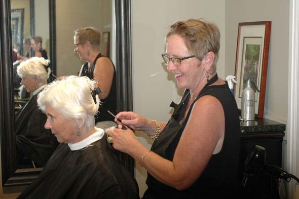 Lori Deal, hair stylist and owner of the recently renovated and renamed Blue Hairon Salon, works with longtime client Linda Sikes, who came to the shop recently in preparation for a family wedding. The salon, which features local, original art in its decor, will open its doors as part of the next village Art Stroll, 6–9 p.m. Friday, Oct. 14. Deal will have refreshments for stroll visitors. (Photo by Carol Simmons)