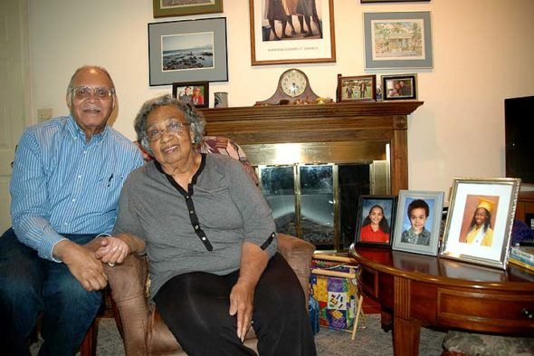 Bob and Olga Harris live in the same Miami Drive home they purchased (for $24,500) almost 50 years ago. They found Yellow Springs an excellent place to raise their three children, whose photos, along with those of their three grandchildren, are proudly displayed in their home. (Photo by Diane Chiddister)