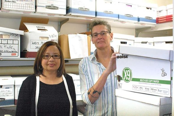 """Village employees Kathy Gudgel, left, and Judy Kintner are primarily responsible for providing public access to Village government records through the Clerk of Council's office. A recent influx of public records requests has kept things hopping. Here, they are pictured with boxes of retired records in a staff supply closet — the """"seamy underbelly"""" of the records office, Clerk Kintner said. (Photo by Audrey Hackett)"""