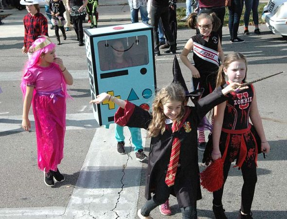 Critters just kept streaming out of the maw of Mills Lawn School. Bringing up the rear, from left, are Miette Murphy, Eloise Murphy,  and Anah Smith watch as wizard Liliana Herzog gestures wildly with her wand, hopefully not transforming co-marcher Alayna Hamilton at her right. (Photo by Matt Minde)