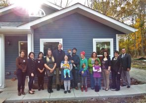 Home, Inc. completed the final two homes in its Cemetery Street project this fall. Homeowners from all four of the project's homes gathered on site, along with community members and Home, Inc. employees and volunteers. Pictured are, from left: Miller Fellow Monika Perry, AmeriCorps VISTA volunteer Cait Bothwell, Development Coordinator Brittany Parsons, homeowners Elizabeth and Matthew Schaade, homeowners Brandy and Patrick Hange with children Nico and Nolan, homeowner Erica Wyant with daughter Rudelle Mae, homeowner Julie McCowan, Miller Fellow Kyna Burke, Executive Director Emily Seibel and Program Manager Chris Hall. (Submitted Photo)