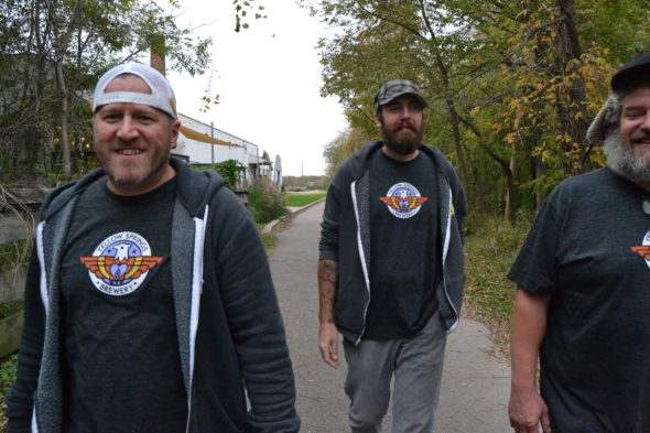"""YS Brewery employees Jon Vanderglas, Chris Hutson and Paul Herzog model the brewery's new logo, to be celebrated this evening at a """"Metamorphosis Party."""" (Submitted Photo)"""