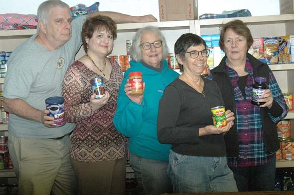 The Yellow Springs Food Pantry, located in the basement of the United Methodist Church, is one of several nonprofits that aim to address the needs of villagers who struggle financially. Shown above are volunteers David Robinow, Bethany Gray, Sue Bothwell, Paula Hurwitz (the pantry's director) and Pat Robinow. The pantry provides food for residents of Yellow Springs and Clifton on the second and fourth Thursdays of the month from 2 to 4 p.m.  (photo by Diane Chiddister)