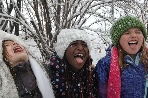 Third-graders Regan Dunn, Ru Robertson and Lily Knopp opened their mouths wide to catch a bit of the surprise snowfall Tuesday morning, Dec. 13, at third- and fourth-grade recess. Eyes, however, were squeezed tight to avoid a direct hit from the massive flakes.  (Photos by Robert Hasek)