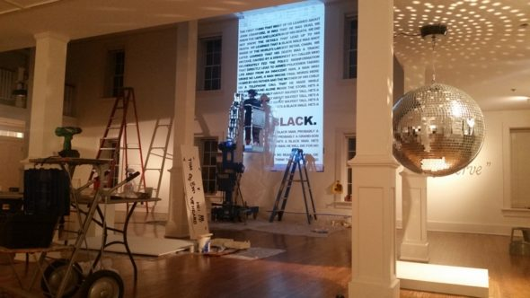 """Living in Divided States exhibition installation with Michael Casselli's US/THEM mirrored disco ball in foreground, Umvikeil G. Scott Jones' """"Suite for John Crawford, III"""" text in background being painted by Syvia Newsome. (Submitted photo)"""