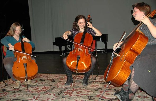 Yellow Springs becomes Cello Springs this week and next, with the debut of a cello festival that runs from Jan. 4–14 and includes several public performances. Pictured from left, festival organizers Lisa Liske-Doorandish, Chiara Enderle and Miriam Liske-Doorandish improvised together at the Foundry Theater before the Friends Music Camp benefit concert last Friday. (Photo by Audrey Hackett)