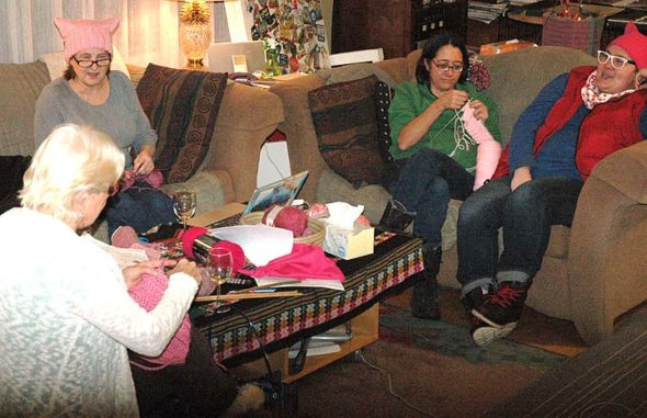 """From left, Linda Sikes, Eve Fleck, Kate Mooneyham and Katie Rose Wright gathered Monday evening at Fleck's home to crochet and knit pink, cat-eared """"pussy"""" hats for participants in the Women's March on Washington, Jan. 21, to wear. The women are participating in the Pussyhat Project, a national initiative tied to the march. Local resident Annie Blanchard is set to host several other hat-making gatherings at the Emporium at 10 a.m. Wednesday, Jan. 11, and Friday, Jan. 13.  (Photo by Carol Simmons)"""