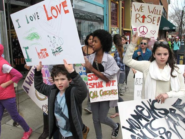 At least 250 villagers took to the sidewalks in downtown Yellow Springs last Saturday, Jan. 21, marching in solidarity with the Women's March on Washington and hundreds of other marches around the country and world. The local Sister March was organized by McKinney Middle School seventh-graders Carina Basora and Ava Schell, who set out to create a positive event for all ages in support of equality and women's rights. Judging by the march's impressive attendance and joyful vibe — and the abundance of young, determined marchers, including, from left, Oskar Dennis, Malaya Booth and Vivian Bryan — they succeeded. (Photo by Matt Minde)