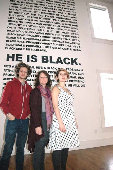 """Standing in front of a wall-size poem by Umvikeli G. Scott Jones are Herndon Gallery Curater Jennifer Wenker, center, and student assistants Daniel Cox and Kathryn Olson. The poem is part of the new exhibit, """"Living in Divided States,"""" which features the work of 50 area artists at Herndon Gallery on the Antioch College campus. (Photo by Diane Chiddister)"""