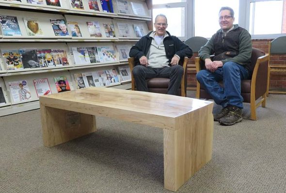 Local woodworker Tom Hawley and local arborist Bob Moore recently sat in front of the new table Hawley made for the Yellow Springs library's periodical room. The table was made with local wood harvested by Moore from ash trees, which were felled by the Emerald Ash Borer. (Submitted photo)
