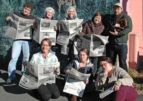 """For the seventh year in a row, the Yellow Springs News won the top prize among weekly newspapers of its size at the Ohio Newspaper Association's annual convention. The paper also came home with 14 individual awards, in categories ranging from editorials to advertising design. Pictured here is the award-winning team of (back row, from left) Matt Minde, Diane Chiddister, Audrey Hackett, Kathryn Hitchcock and Dylan Taylor-Lehman, as well as (front row, from left) Robert Hasek, Suzanne Szempruch and Lauren """"Chuck"""" Shows. (Photo by Matt Minde, Suzanne Szempruch and the timer)"""