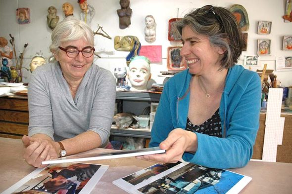 Local artists Beth Holyoke, left, and Kaethi Seidl spent a month in a Greek refugee camp in February. Back home in Holyoke's Yellow Springs studio, they looked over photos of some of the children they worked with at the camp. (Photo by Diane Chiddister)
